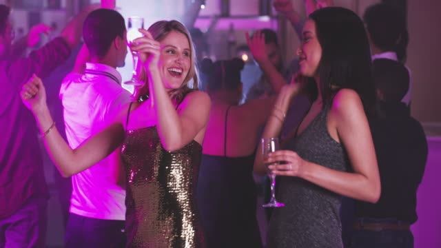 Good friends, great night 4k video footage of two young women toasting with their drinks while dancing in a nightclub party social event stock videos & royalty-free footage
