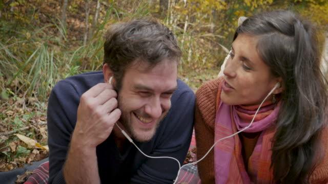 iyi görünümlü çift birlikte aynı kulaklıklar paylaşımı müzik dinlerken - kulak i̇çi kulaklık stok videoları ve detay görüntü çekimi