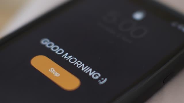 god morgon väckarklocka på telefonen, närbild. hållplats för handavlyssning. - alarm clock bildbanksvideor och videomaterial från bakom kulisserna