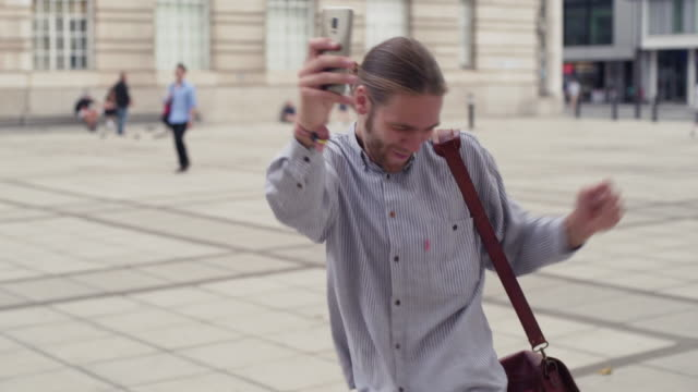 Good news city dance Stock video clip of a young, bearded man reading a message on his phone while walking across a city square. The message is clearly very good news and he starts dancing with delight. good news stock videos & royalty-free footage