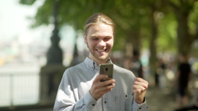 Good news city trees Stock video clip of a long haired young man receiving very good news on his phone as he walks along a sunlit urban glade of trees. He's surrounded by out of focus people as becomes overjoyed with what he's just seen on his phone. test results stock videos & royalty-free footage
