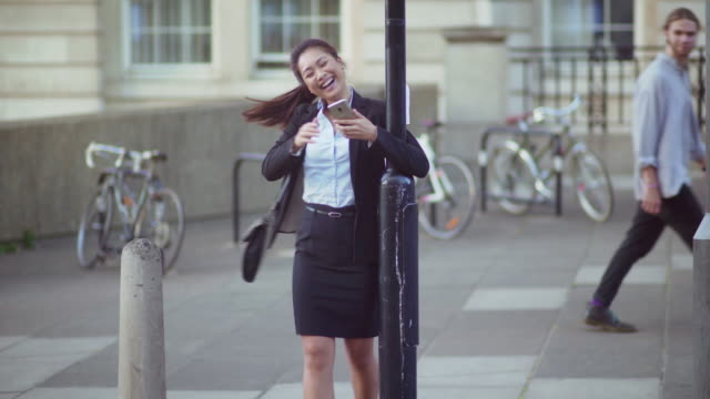 Good news city worker 4k stock video clip showing a young Asian woman in office clothes receiving a message on her phone. The message is very good news & she becomes dynamically elated a swings around 2 lamp posts, a young man walking past smiles with amusement. good news stock videos & royalty-free footage
