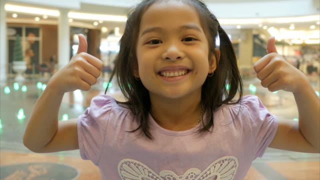 asyalı küçük kız iyi işareti - thumbs up stok videoları ve detay görüntü çekimi