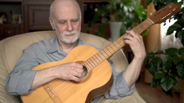 Good-looking handsome senior man in t-shirt sitting in chair at home and playing guitar Good-looking handsome smiling senior man in light-colored t-shirt sitting in yellow chair at home and playing guitar lounge chair stock videos & royalty-free footage