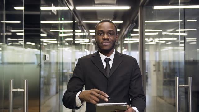 vídeos de stock, filmes e b-roll de bom e sério empresário de pele escura caminhando para seu local de trabalho através do corredor do escritório, usando tablet pc e olhando para a câmera - alto descrição geral