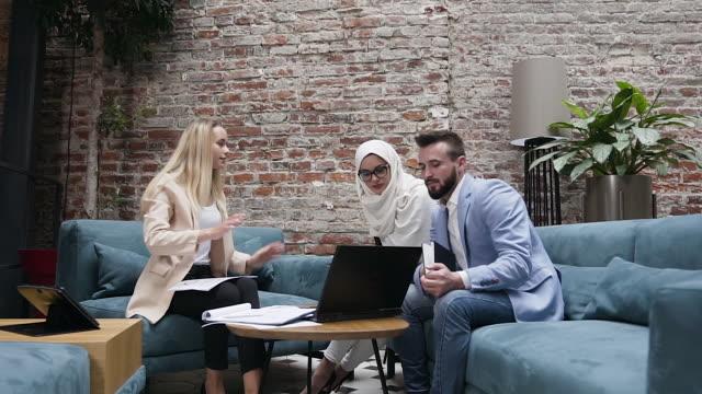 gut aussehende junge geschäftsleute aus der ethnischen zugehörigkeit arbeiten im rahmen ihres finanzprojekts im modernen büro zusammen - menschliches gelenk stock-videos und b-roll-filmmaterial
