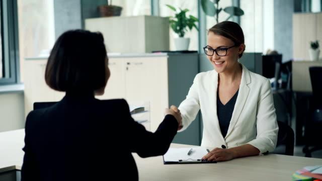 vídeos de stock, filmes e b-roll de boa aparência jovem do departamento de recursos humanos está a entrevistar um profissional feminino, cumprimentando-se então a fazer perguntas e escrever. conceito de emprego e da juventude. - rh