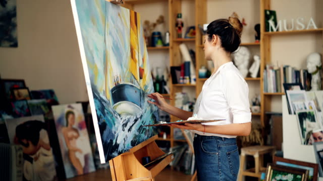 Good-looking young woman in casual clothing is painting in workroom then looking at picture, evaluating her work and smiling enjoying beautiful image.
