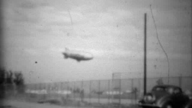 1938: Goodyear lifeguard tire blimp flying above classic car.
