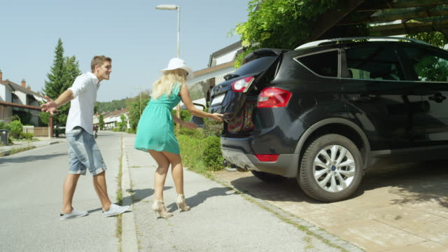 Goofy woman tries to convince boyfriend to stuff more suitcases in their SUV. Goofy Caucasian woman tries to convince her frustrated boyfriend to stuff more suitcases in their SUV before leaving their suburban home. Funny argument between newlyweds over packing too much baggage stuffed stock videos & royalty-free footage