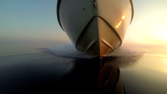 gopro: view of a speedboat bow while floating on water at sunset - lakes stock videos and b-roll footage