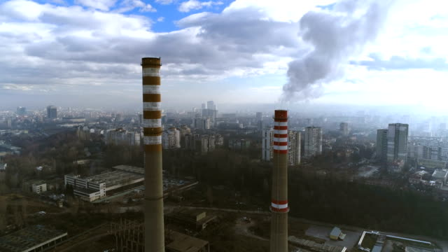 Gorgeous aerial drone shot flying between two heavy industry factory chimneys video