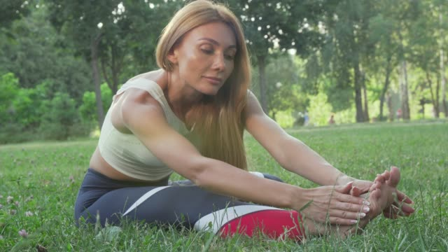 Gorgeous athletic woman stretching outdoors smiling to the camera