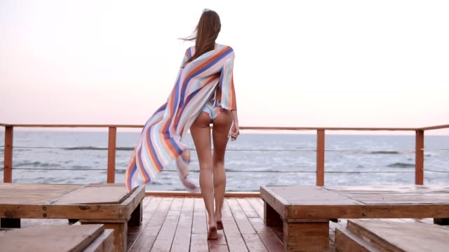 Gorgeous backside slow motion footage of a caucasian model in swimsuit and summer cardigan walks by wooden floor outdoors, wind waving her cloth. Sea or ocean on the background