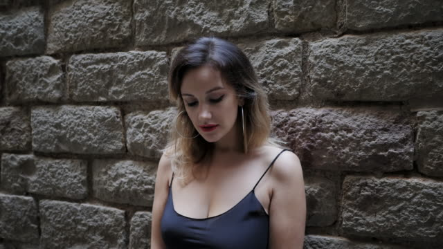 Gorgeous blonde alluring woman in black dress with passionate red lips in gothic quarter of Barcelona. Natural beauty, female portrait, seductive look. Being self-confident. 4k video