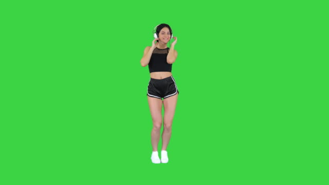 Gorgeous brunette lady listening music in headphones on a Green Screen, Chroma Key