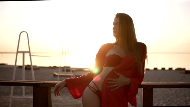 Gorgeous caucasian model in red beautiful swimsuit standing near the railing on the beach. Sun shines and blurred bright water on the background video