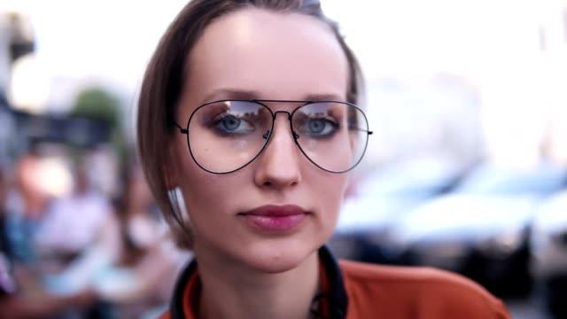 vídeos de stock, filmes e b-roll de lindo close-up vista de uma menina jovem, loira, olhando para a câmera e sorrindo, usando um óculos modernos. feliz e despreocupada. ao ar livre - camera