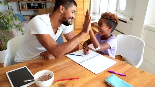 wspaniała córka kończy pracę domową z ojcem rano - praca domowa filmów i materiałów b-roll