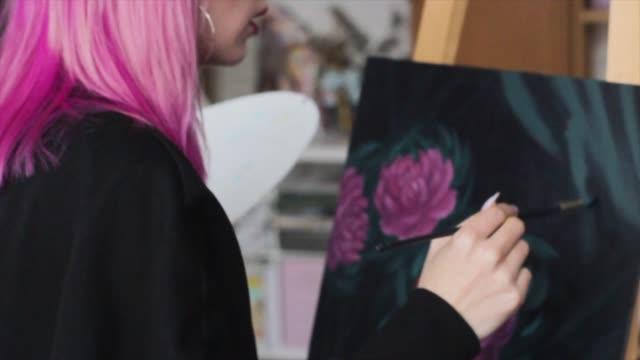 stockvideo's en b-roll-footage met prachtige vrouwelijke kunstenaar met roze haar werken aan kunstprojecten met palet in haar handen in de art studio. jonge vrouw tekent een foto - roze haar