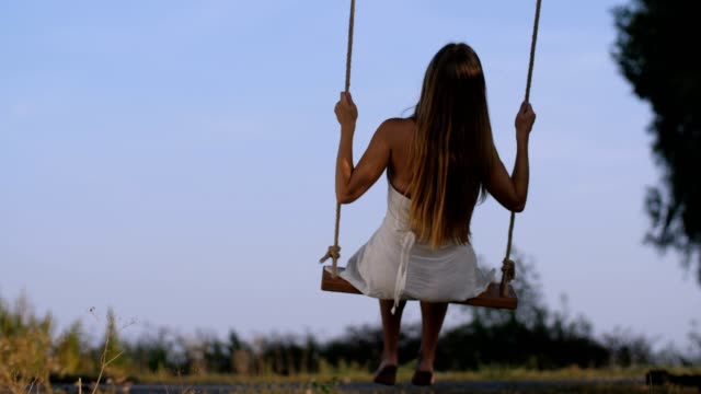 Gorgeous female in childish mood swinging in nature
