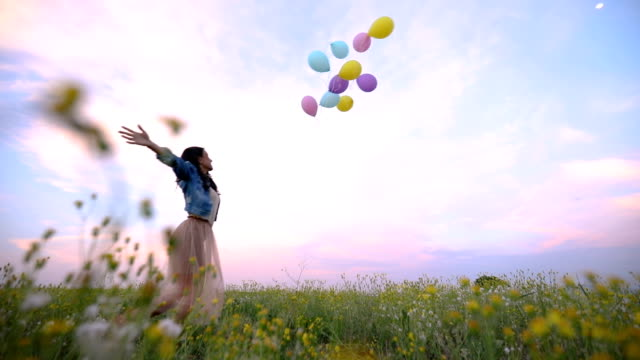 gorgeous girl in denim jacket letting go of balloons - vivere semplicemente video stock e b–roll
