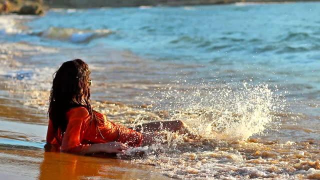 великолепные девушки, лежа на пляж и волны брызг тела - загар стоковые видео и кадры b-roll