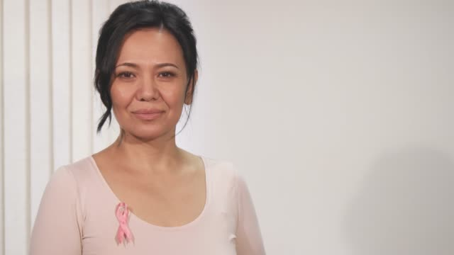 Gorgeous happy mature Asian woman smiling to the camera Happy beautiful mature Asian woman wearing pink ribbon breast cancer awareness symbol smiling to the camera copyspace positivity vitality joy wellbeing health prevention patient. mammogram stock videos & royalty-free footage