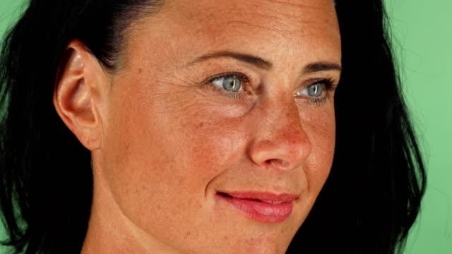 Hermosa mujer madura feliz con hermosos ojos sonriendo a la cámara - vídeo