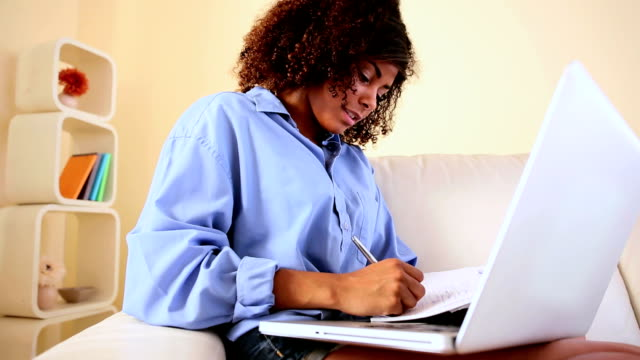 Gorgeous happy student sitting on couch studying video