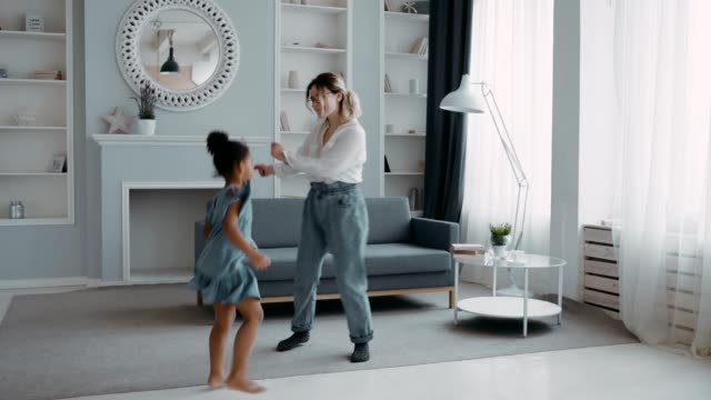 vídeos de stock e filmes b-roll de gorgeous joyful mother jumping funny kid african daughter dancing together in apartment with sofa, caring mother having fun and cool time dressed in white shirt dress concept multinational family - hygge