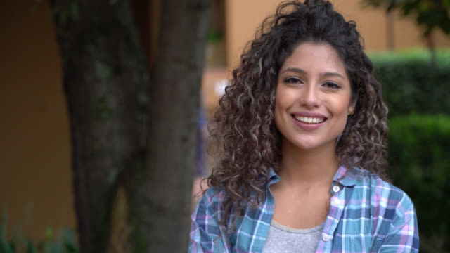 Gorgeous latin american student with curly hair looking at camera smiling Gorgeous latin american student with curly hair looking at camera smiling very happy university student stock videos & royalty-free footage