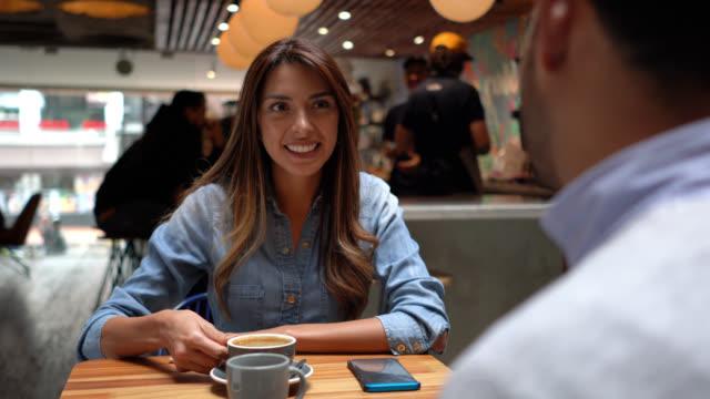 ursnygg latinamerikansk kvinna på dejt med en oigenkännlig man njuta en kaffe samtidigt talande - colombia bildbanksvideor och videomaterial från bakom kulisserna