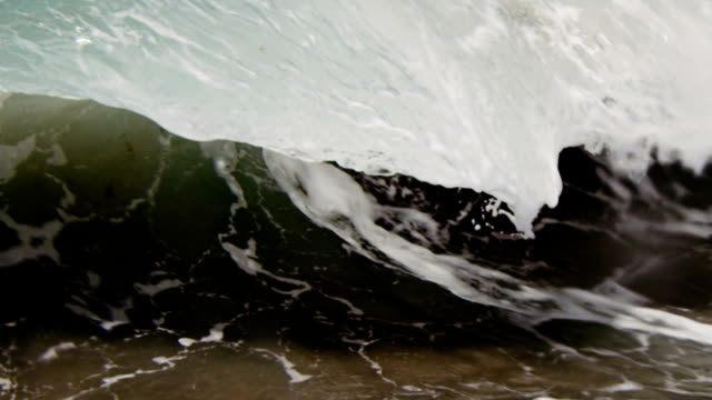 Gorgeous lip of wave that looks like a thin sheet of glass gliding into the camera on the shallow sand beach in the California summer sun. Shot in slowmo on the Red Dragon at 300FPS. video