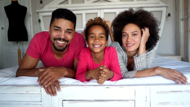 gorgeous mixed race family in bed - perfezione video stock e b–roll