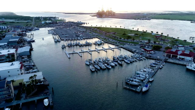 Gorgeous sunset on Texas gulf coast at marina boat dock at Port Aransas , TX aerial drone view above Ship channel and Gulf of Mexico
