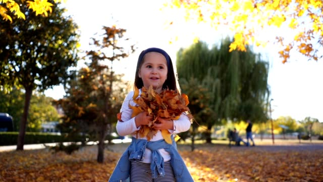 Gorgeous toddler girl throwing leaves at a city park in autumn