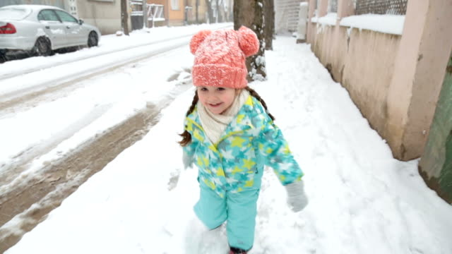 Gorgeous toddler running on a snowy day Cute and lovely toddler in a winter jacket running on the sidewalk of the street in winter. candid stock videos & royalty-free footage