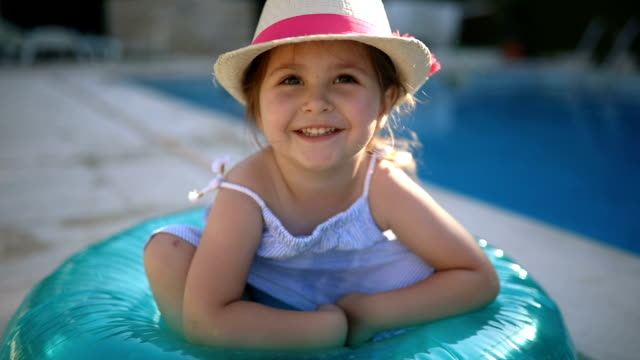 Gorgeous toddler sitting in a inflatable ring Cute and gorgeous young girl, having fun at the swimming pool, enjoying the summer. pointing stock videos & royalty-free footage