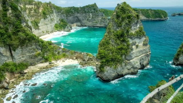Traumhafte Aussicht rollenden Wogen, die Felsen und Sandstrand auf der Unterseite mit transparente Meerwasser in Nusa Penida, Nordküste, Bali, Indonesien – Video
