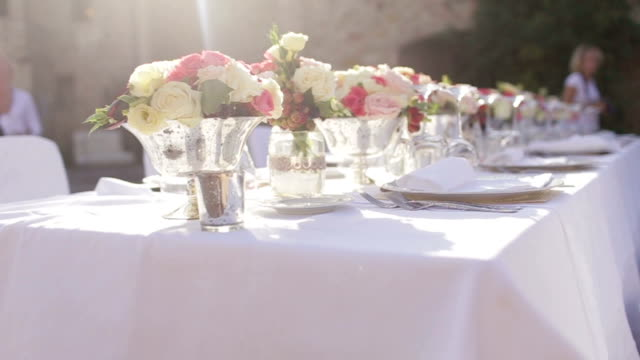 Gorgeous wedding  table setting for fine dining outdoors decorated with flowers video