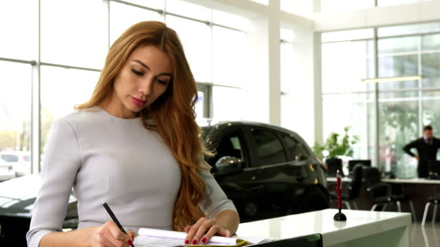 Gorgeous woman buying a new car at the dealership smiling to the camera video