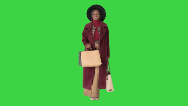 Video Gorgeous woman in a hat posing with shopping bags smiling on a Green Screen, Chroma Key