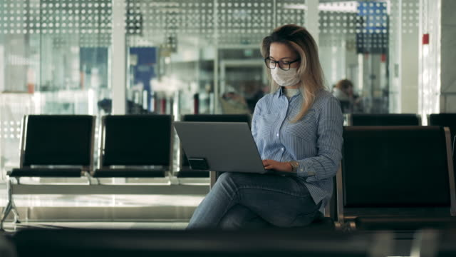 Gorgeous woman in a safety mask is working on a laptop video