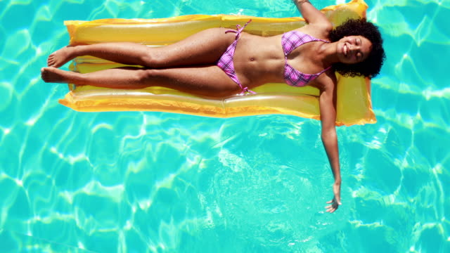 Gorgeous woman lying on lilo in swimming pool Gorgeous woman lying on lilo in swimming pool on her holidays sunbathing stock videos & royalty-free footage