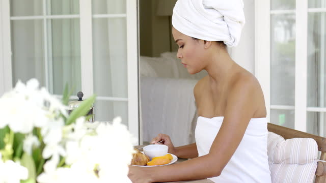Gorgeous woman wrapped in towel sitting at table Single gorgeous woman wrapped in towel sitting at table with juice  breakfast snack and flower bouquet outside of hotel room wearing a towel stock videos & royalty-free footage