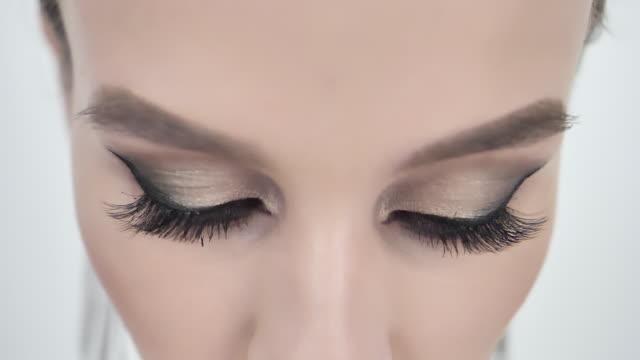 gorgeous woman's eyes with long eyelashes glamorous makeup - kosmetyczka praca w salonie piękności filmów i materiałów b-roll