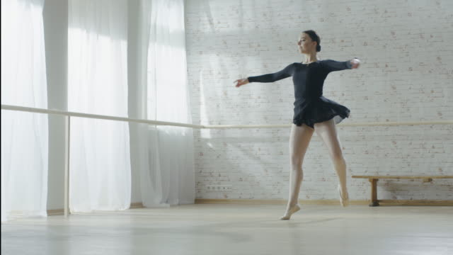 gorgeous young ballerina doing pirouette in slow motion. shot in a bright modern studio on a sunny day. - praticare video stock e b–roll