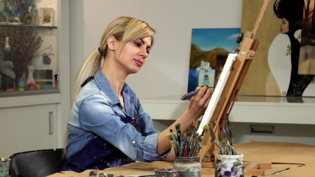Gorgeous young female artist working on her painting at the Art Studio video