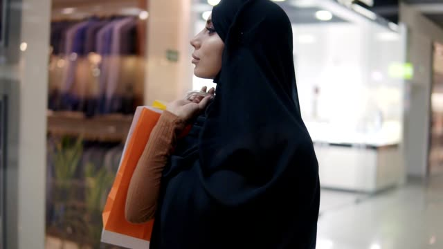 gorgeous young muslim woman in black hijab with different bags on her shoulder walking by shopping mall. slow motion. arabic, confident woman enjoying shopping time, smiling - личный аксессуар стоковые видео и кадры b-roll